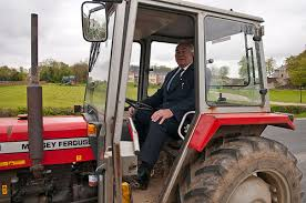 guy in a suit driving a tractor